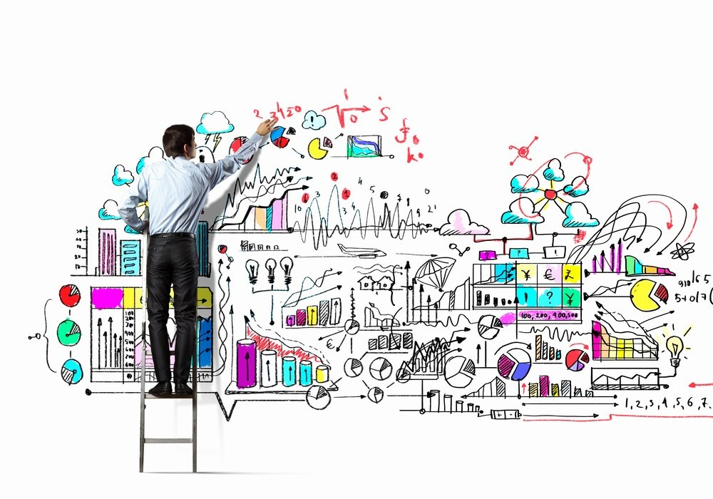 Back view of businessman drawing marketing plan on wall