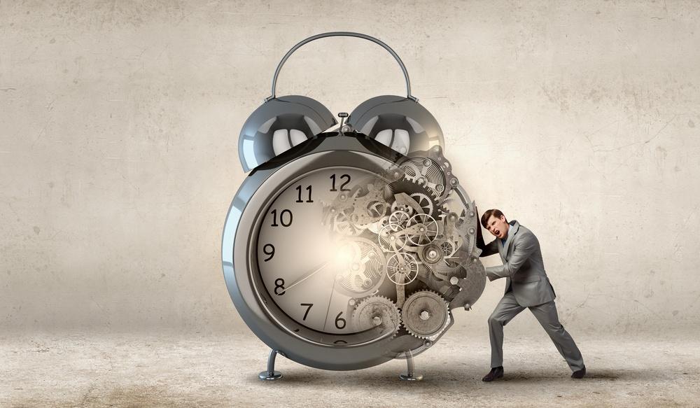 Slow websites: Businessman making effort to move alarm clock