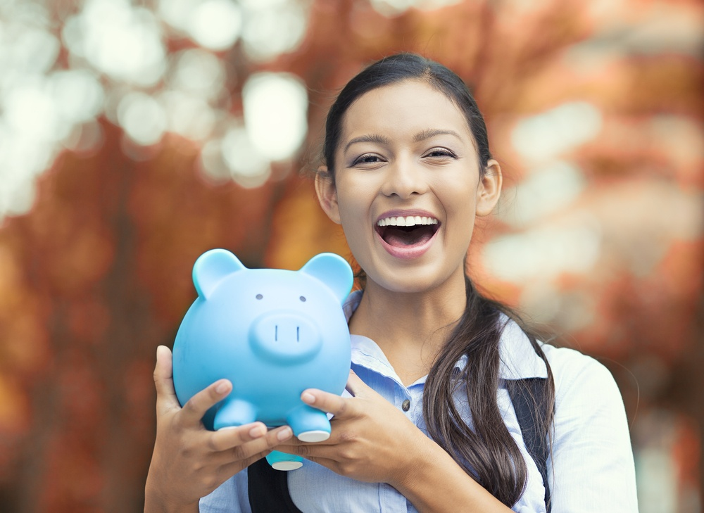 PPC costs smiling business woman, bank employee holding piggy bank