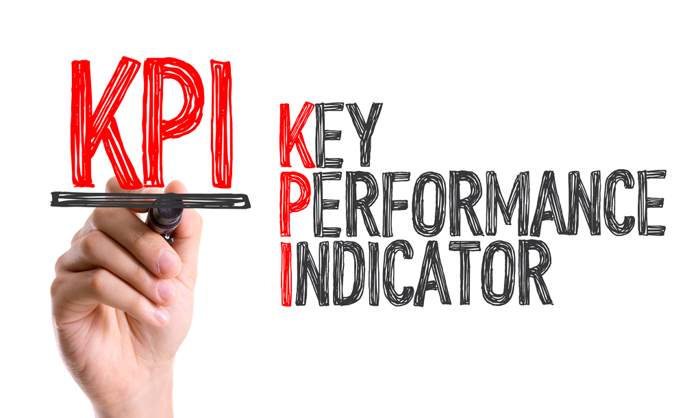Hand with marker writing KPI. Importance of reporting and measuring