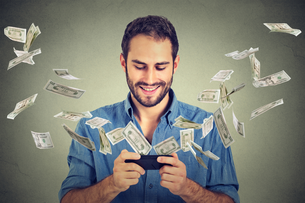 Getting more customers through paid efforts. Technology, e-commerce concept. Happy young man using smartphone with dollar bills flying away from screen isolated on gray wall office background.