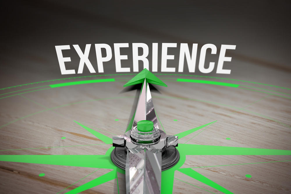 The word experience and compass against brown wooden background