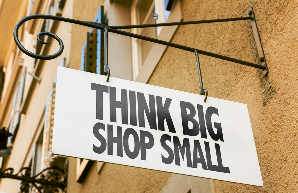 Small company ppc adverts. Think Big Shop Small sign in a conceptual image