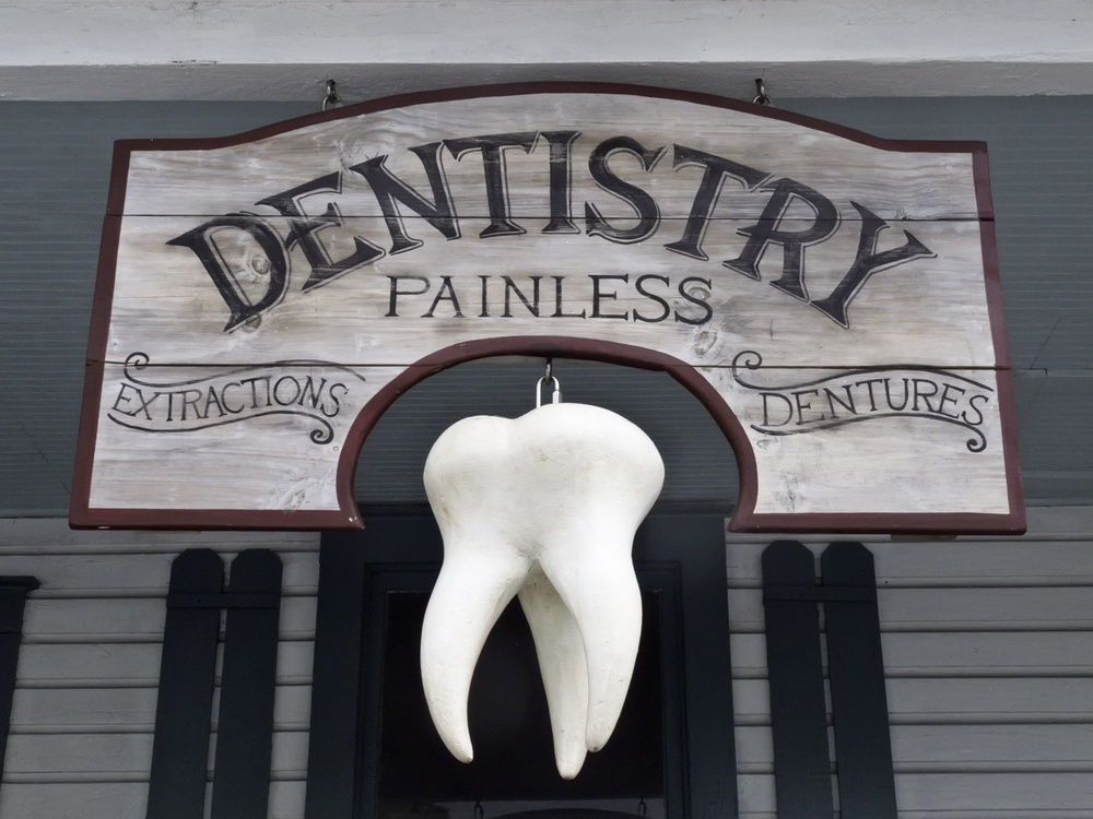 Vintage sign with giant tooth hanging in front of dentist's office