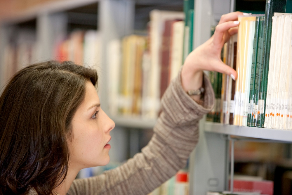 Woman looking for a book at the library