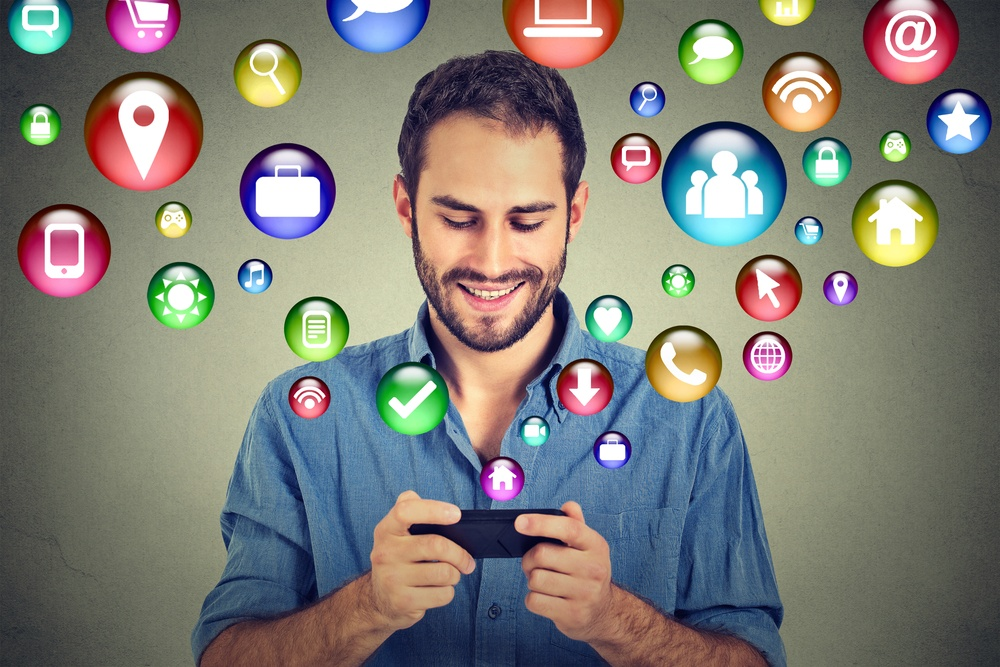 mobile web communication technology mobile phone high tech concept. Happy man using texting on smartphone social media application icons flying out of cellphone isolated grey wall background. 4g data plan