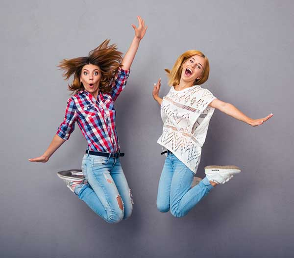 Two cheerful marketers jumping
