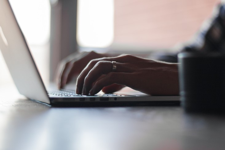 Blogger writing an article on a laptop computer for a marketing blog